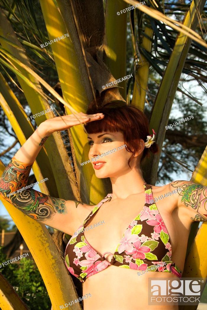 Stock Photo: Portrait of sexy redheaded woman in bikini with palm tree.