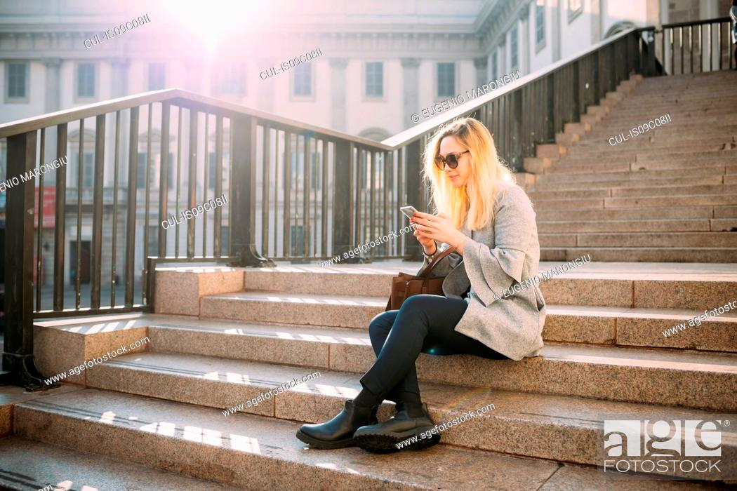 Stock Photo: Young woman sitting on city stairway looking at smartphone, Milan, Italy.