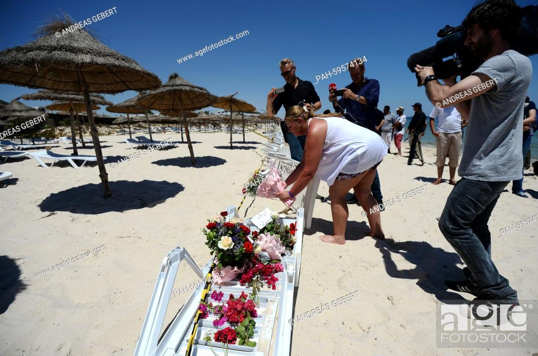 A Woman Lays Flowers For The Victims On Beach Of