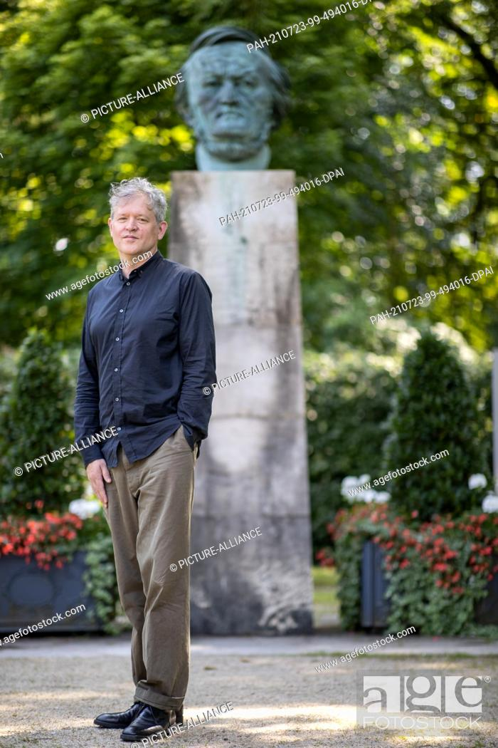 """Stock Photo: 23 July 2021, Bavaria, Bayreuth: US director Jay Scheib stands in front of a bust of Richard Wagner. Scheib is showing """"""""Siegfried's"""""""" dragon fight in virtual."""
