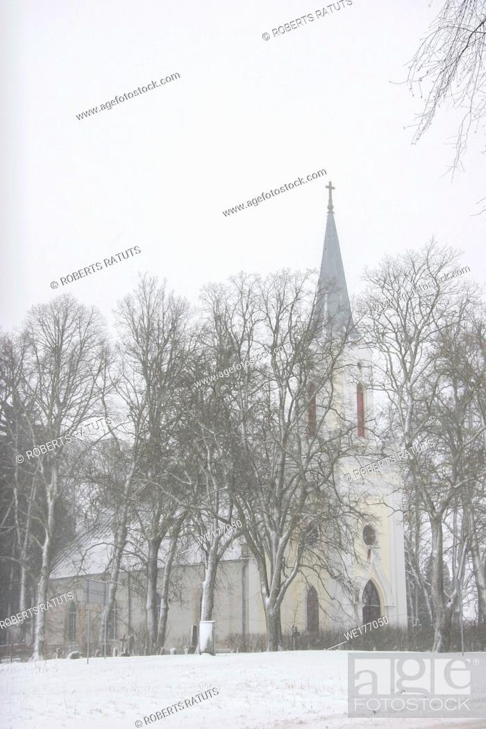 Imagen: Church in snowfall. Winter in Barbele, Latvia. Church covered in snow. Winter landscape with snow covered church and trees. . .