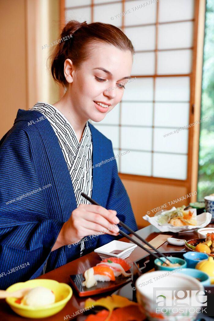 Stock Photo: Caucasian woman wearing yukata eating at traditional ryokan, Tokyo, Japan.
