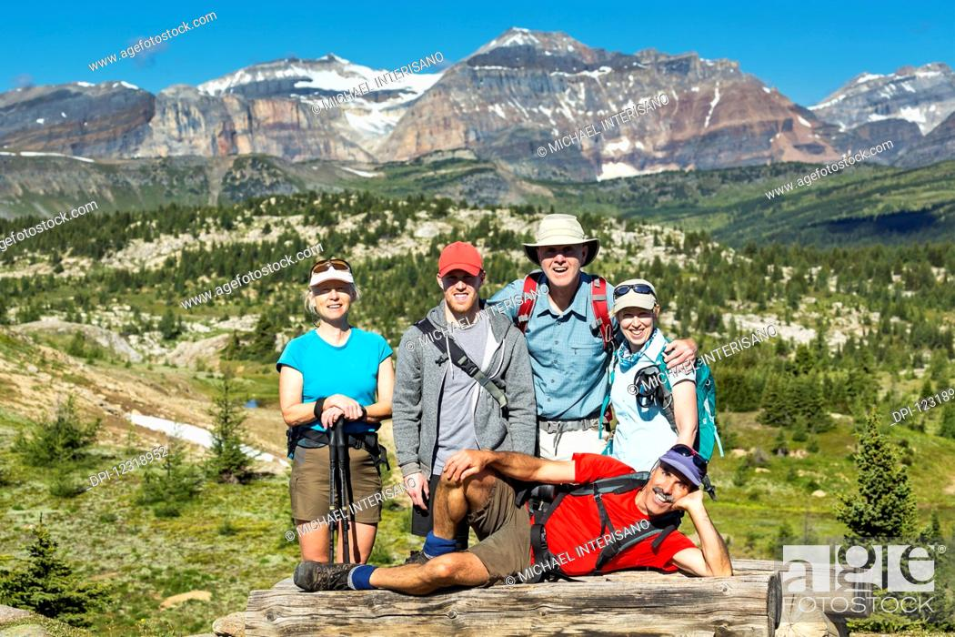 Stock Photo: Group of hikers posing on a log bench with valley below and mountains and blue sky in the distance; Banff, Alberta, Canada.