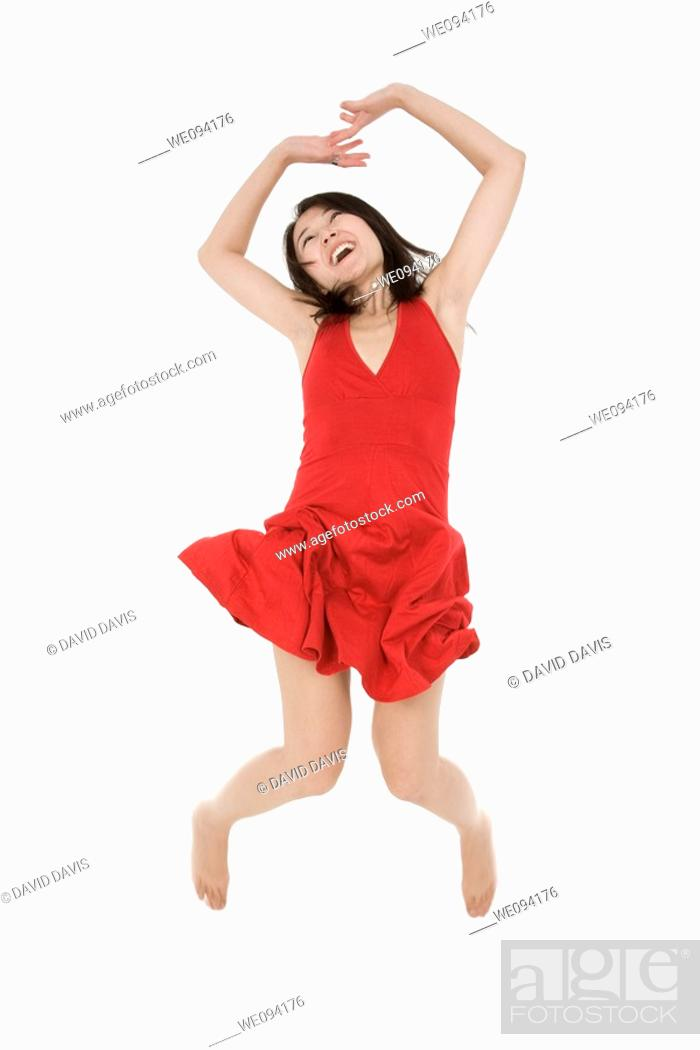 Stock Photo: Beautiful Asain woman in a red sundress jumping on a white background.