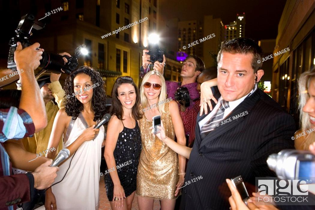 Stock Photo: Small group of young women and bodyguard surrounded by paparazzi.