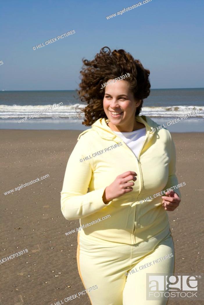 Stock Photo: Woman jogging on beach.