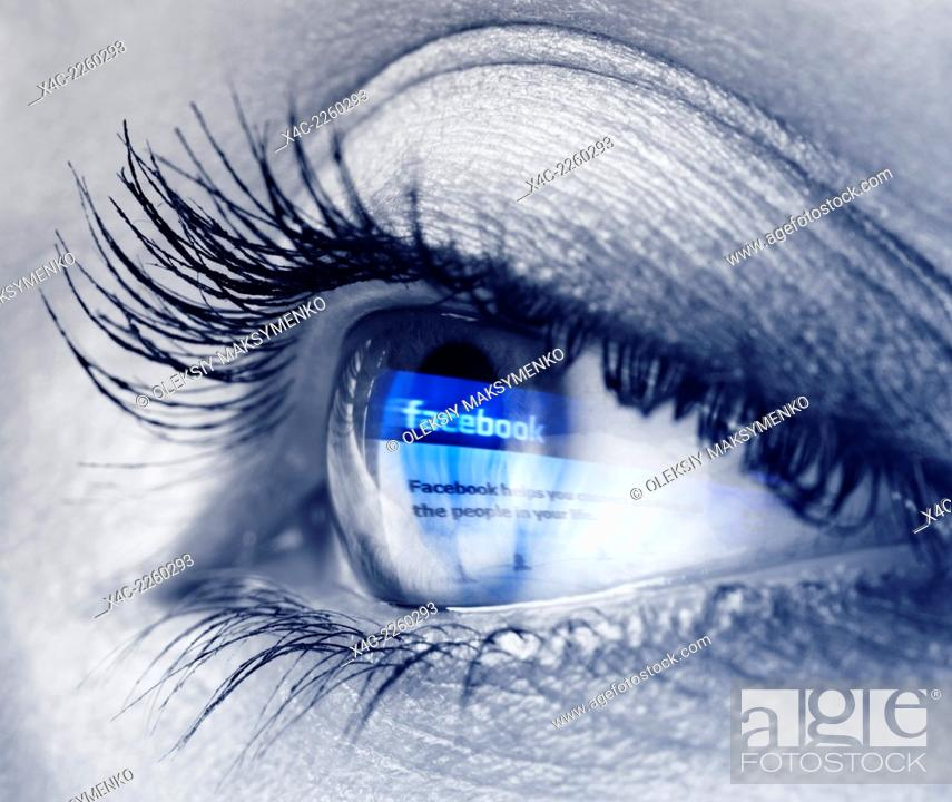 Stock Photo: Closeup of a young woman blue eye with Facebook logo reflecting in it. Black and white with blue.