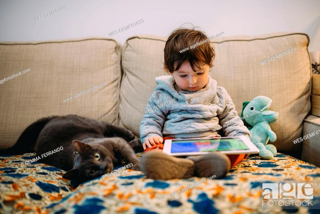 Stock Photo: Baby girl sitting on couch watching videos on a tablet with a cat.
