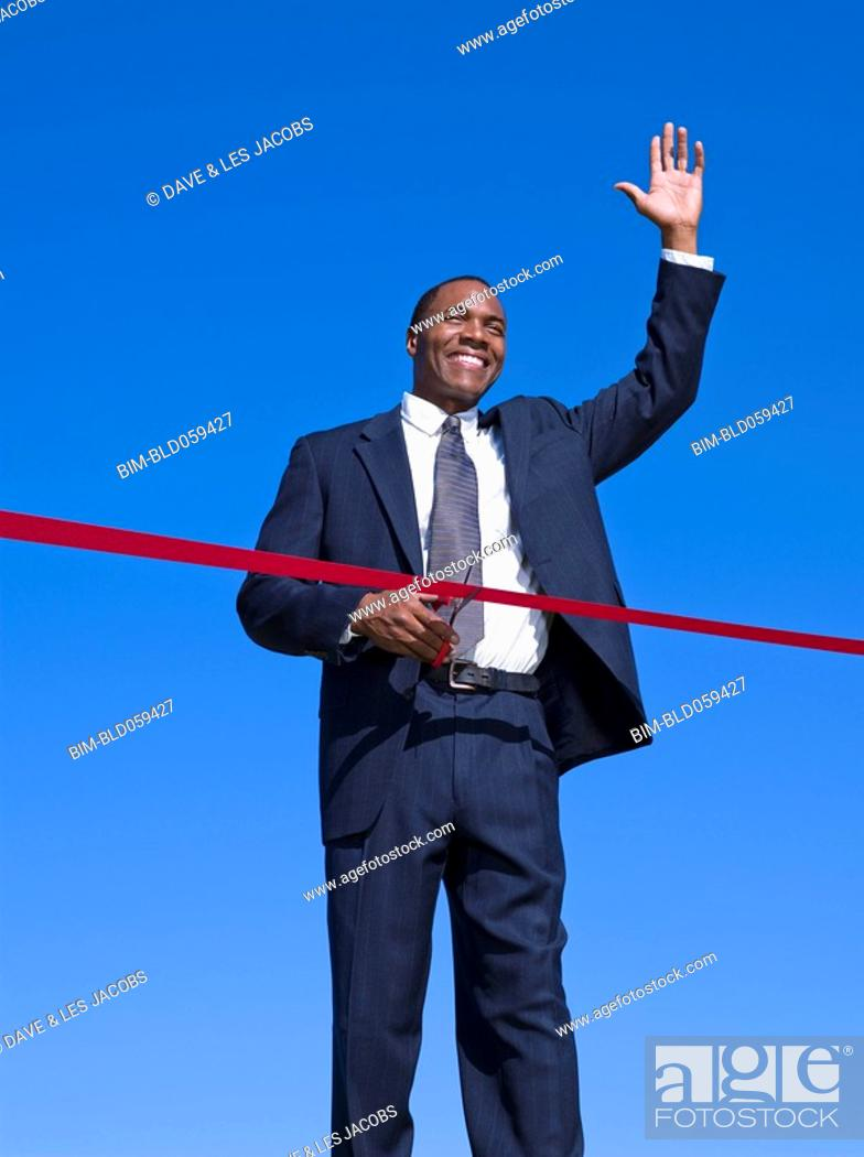 Stock Photo: African businessman cutting ribbon.