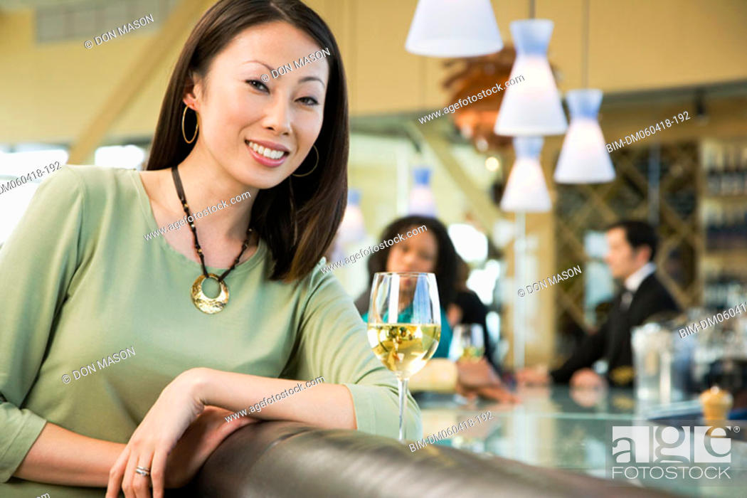 Stock Photo: Woman at bar with glass of wine.
