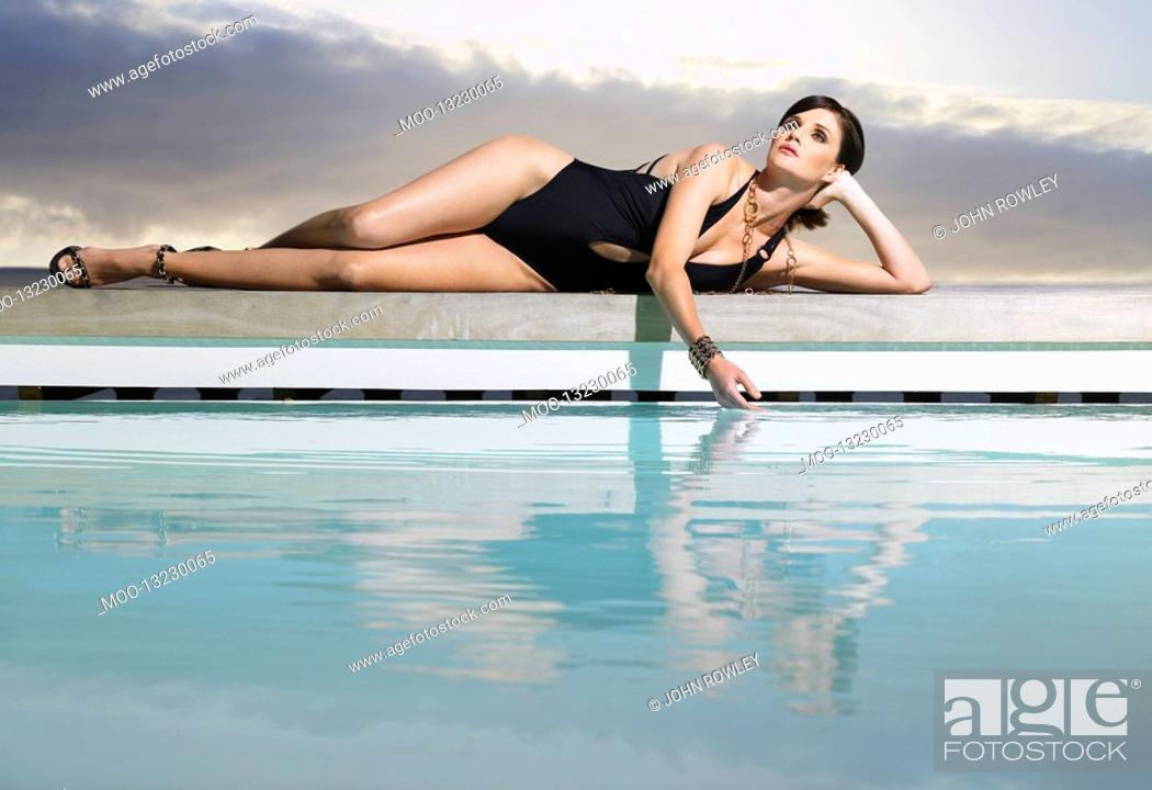 Stock Photo: Woman in bathing suit reclining by pool.