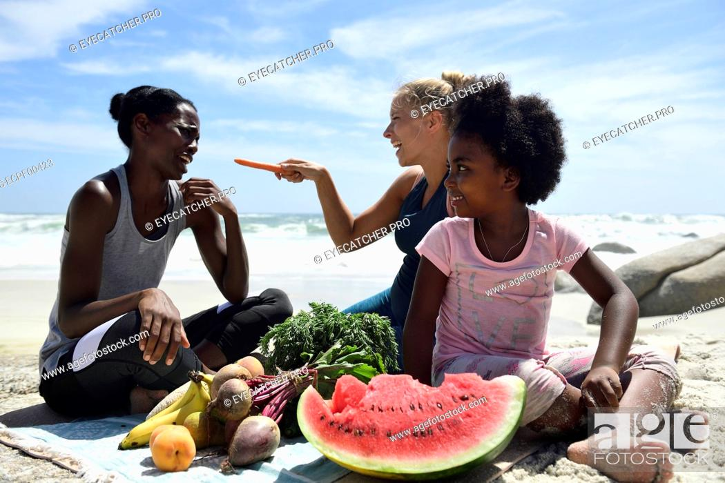 Stock Photo: Mother with daughter and friend having a picnic on the beach.