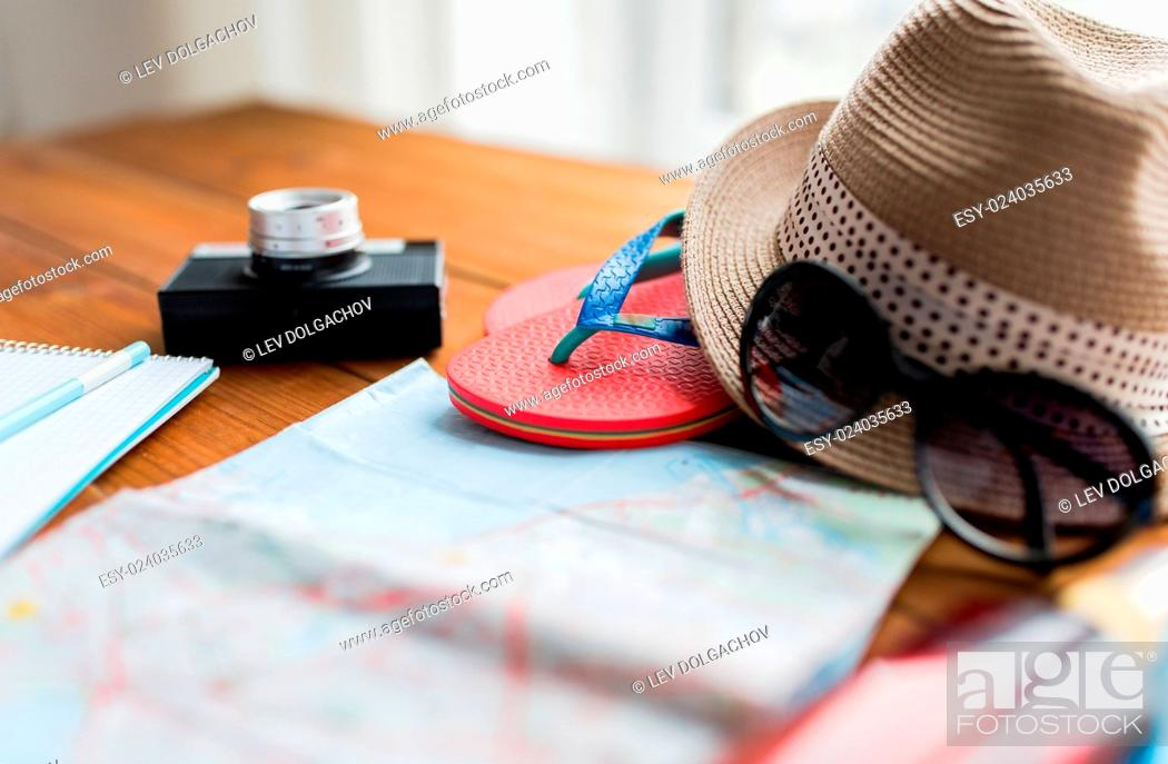 Stock Photo: summer vacation, tourism and objects concept - close up of travel map, flip-flops, hat and camera on wooden table at home.