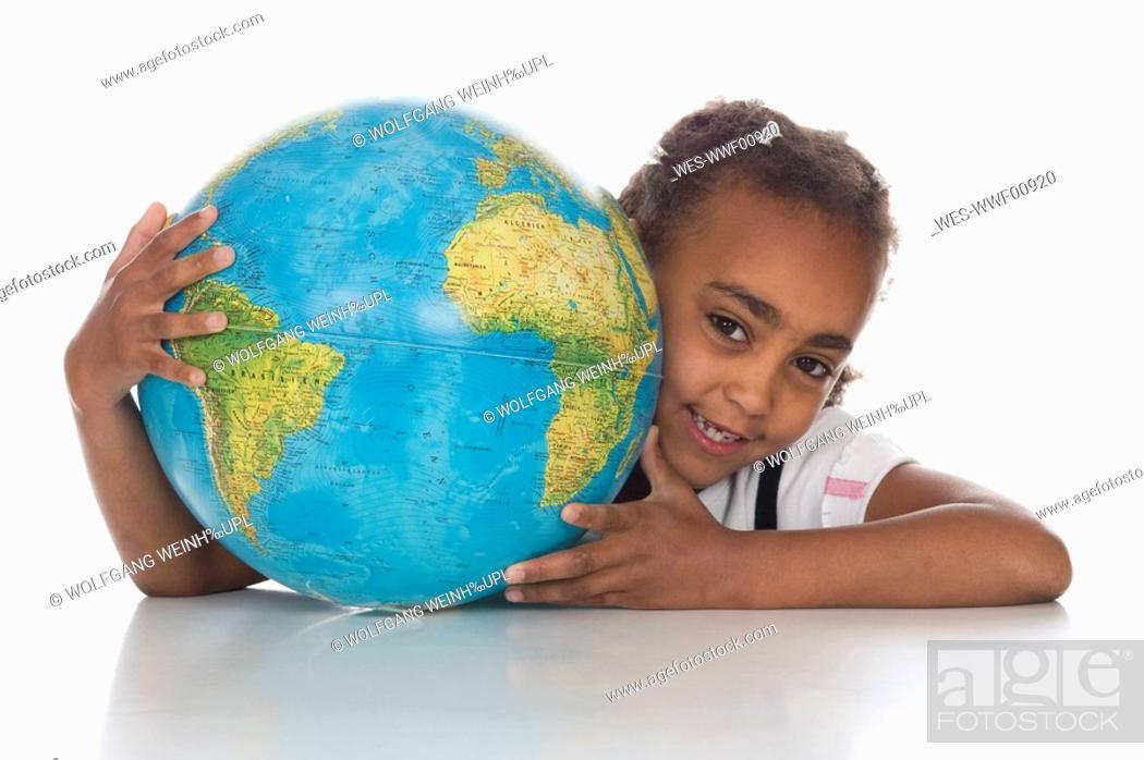 Stock Photo: African girl 6-7 holding globe, smiling, portrait.
