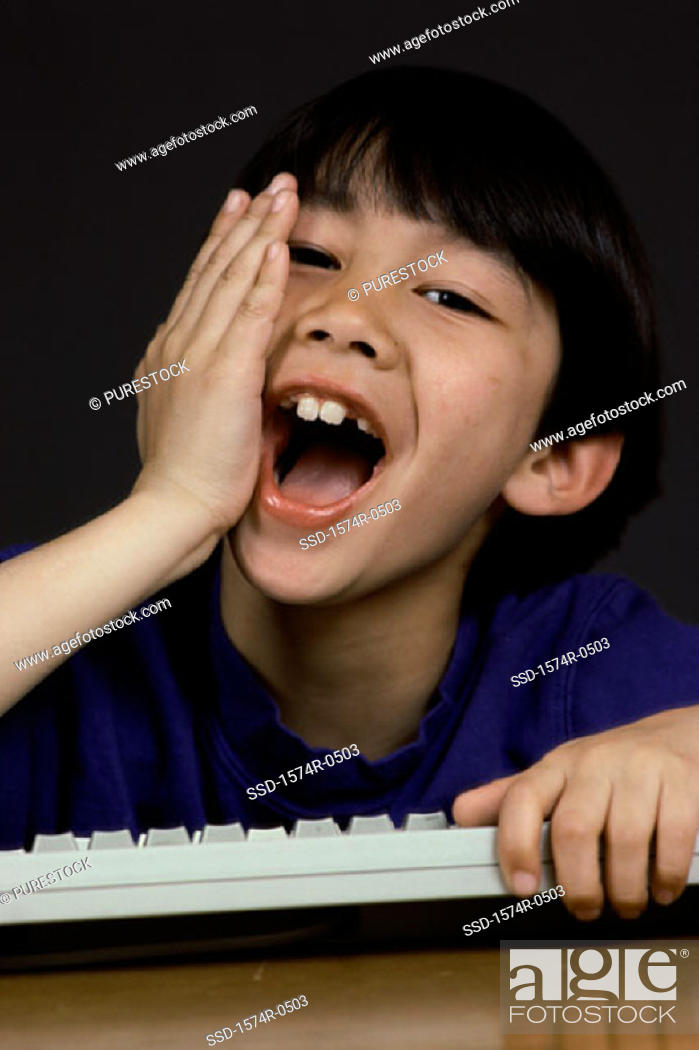 Stock Photo: Portrait of a boy holding a computer keyboard laughing.