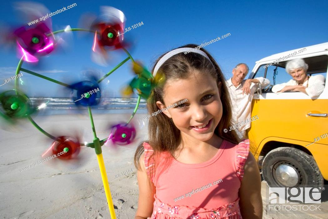 Stock Photo: Girl 7-9 with pinwheel on beach, grandparents and camper van in background, smiling, portrait.
