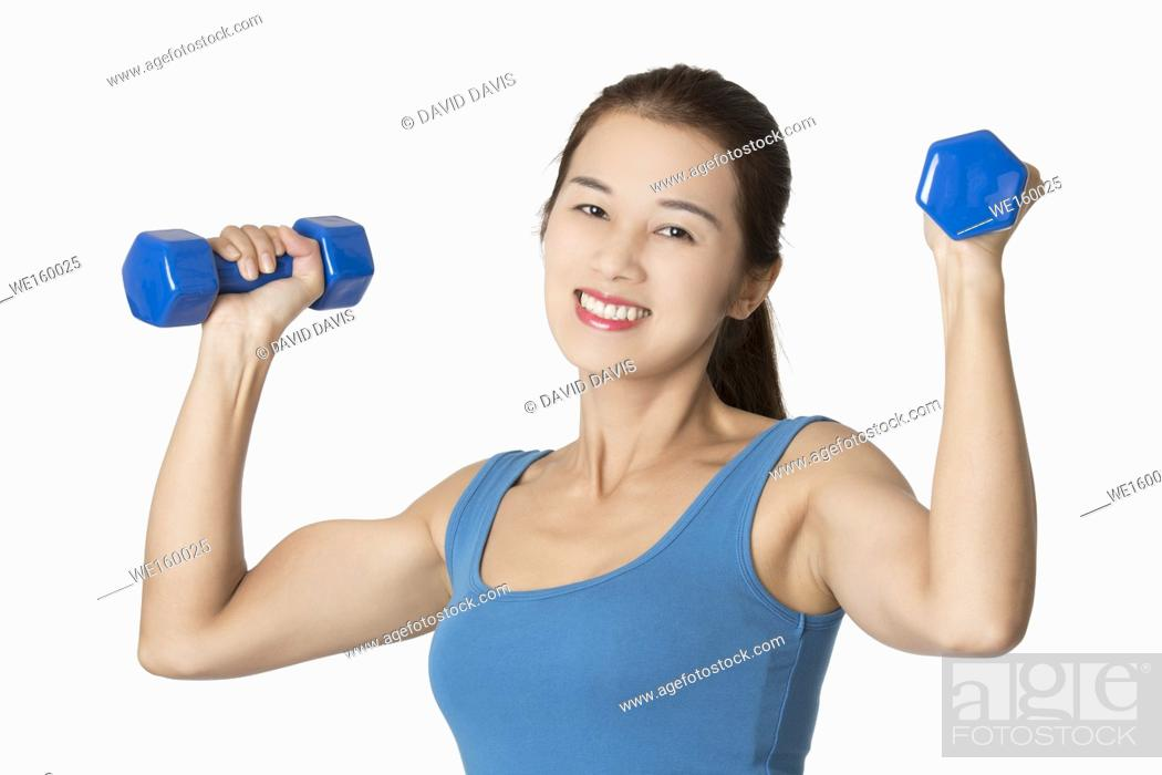 Stock Photo: Beautiful Asian woman working out using dumbbell weights isolated on a white background.