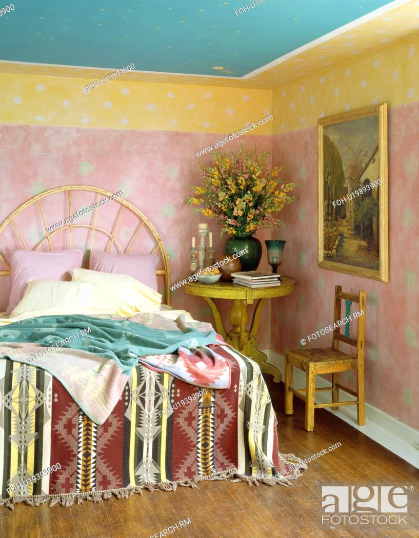 Stock Photo Painted Pink And Yellow Walls In Ethnic Style Bedroom With Kelim Throw On Bed