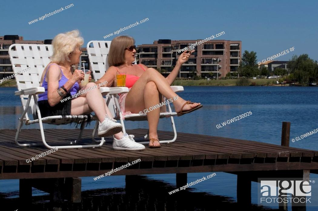 Stock Photo: Two senior women sitting on chairs at the boardwalk.