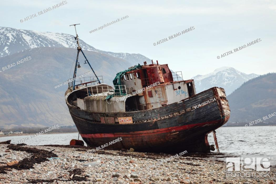 Stock Photo: A boat stranded in the loch Linnhe on Fort William, on the center of Scottish Highlands, Ben Nevis at the back.