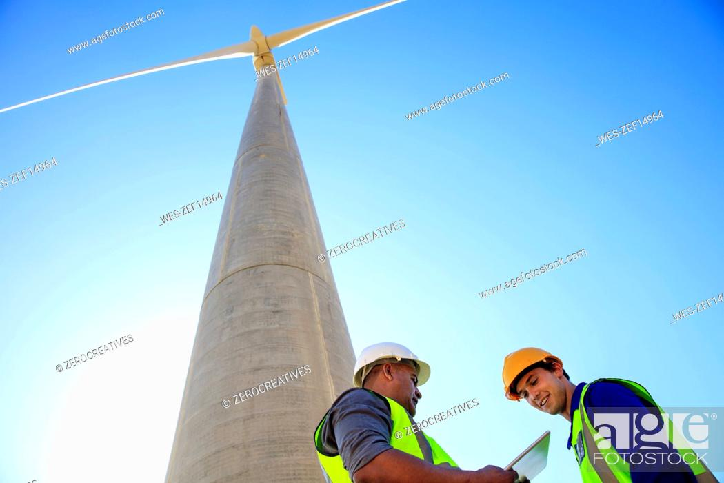 Stock Photo: Low angle view of technicians with tablet in front of wind turbine.