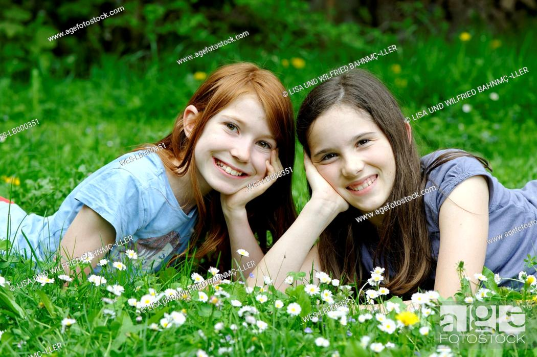 Stock Photo: Girls are lying in a flower meadow.