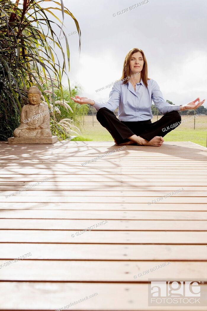 Stock Photo: Businesswoman doing yoga in a park.