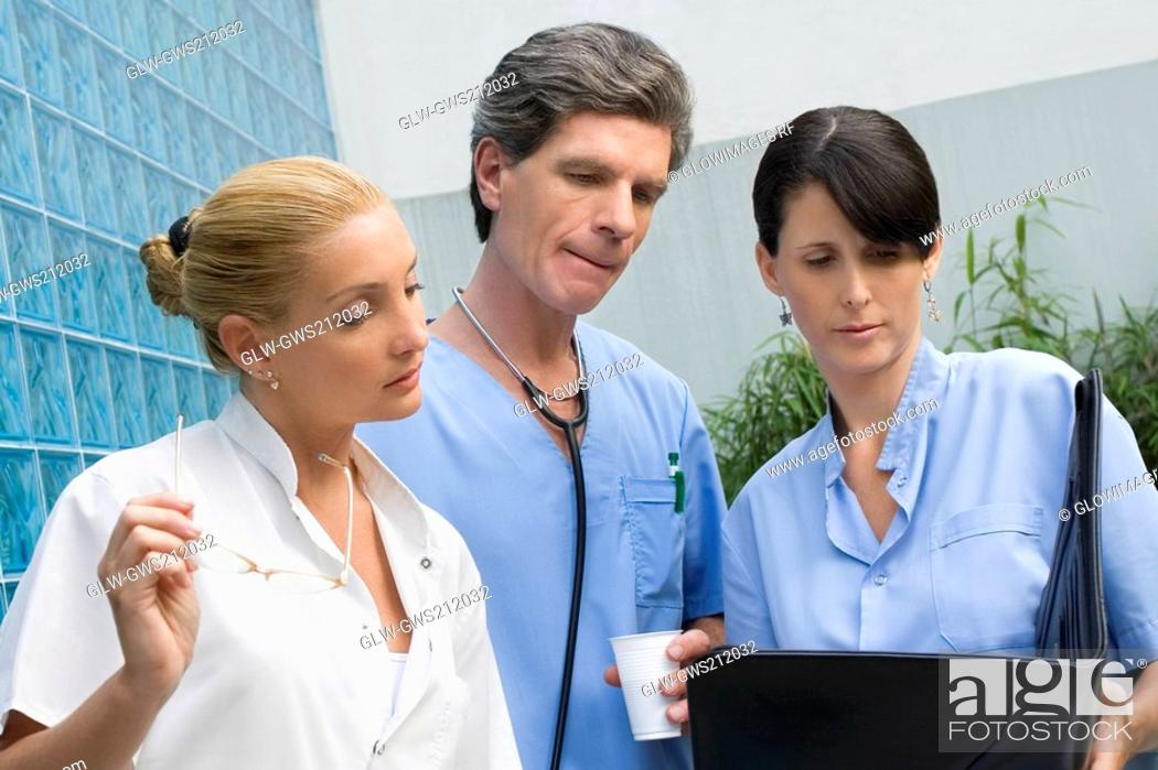 Stock Photo: Two female surgeons and a male doctor discussing a medical report.