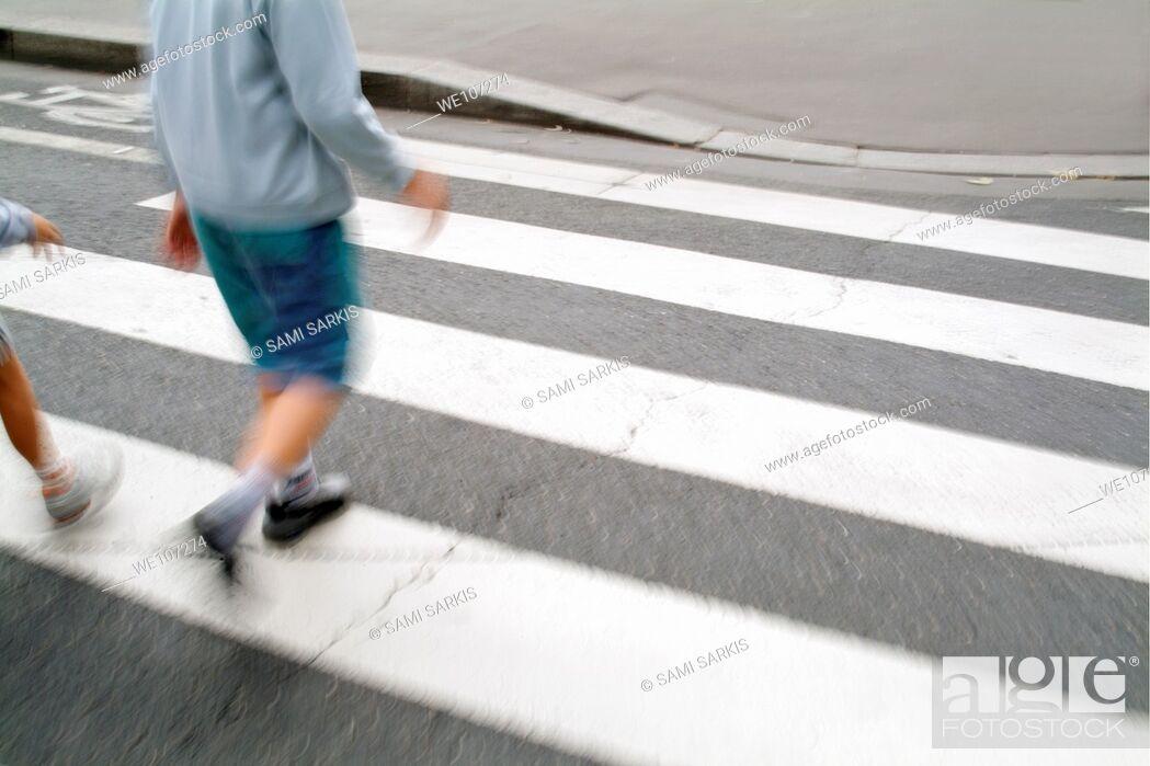 Stock Photo: Children walking across a zebra crossing on a city street, Paris, France.