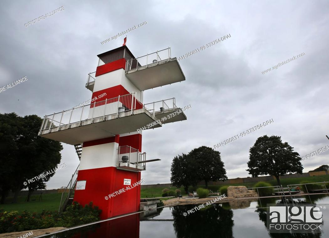 Stock Photo: 31 August 2020, North Rhine-Westphalia, Essen: Dark clouds pass by the diving tower of the natural outdoor pool. The predominantly cool and cold weather from.