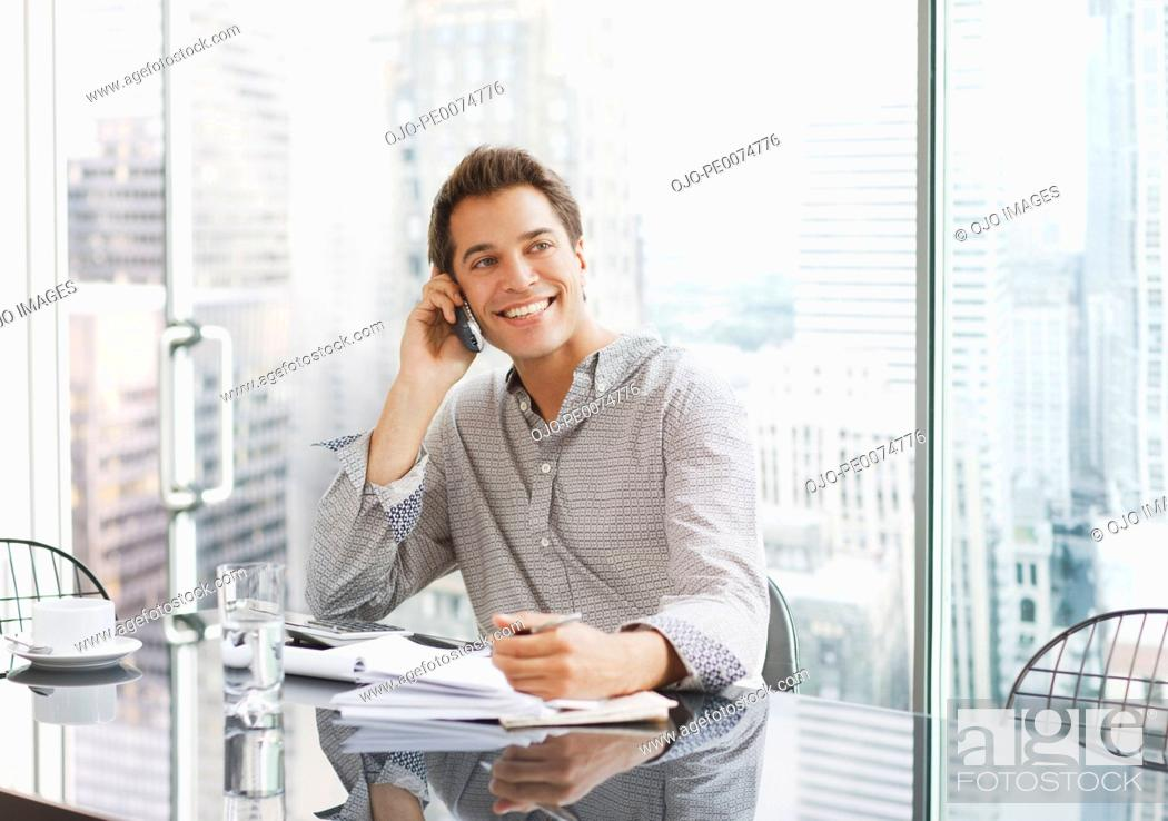 Stock Photo: Businessman using cell phone at desk.