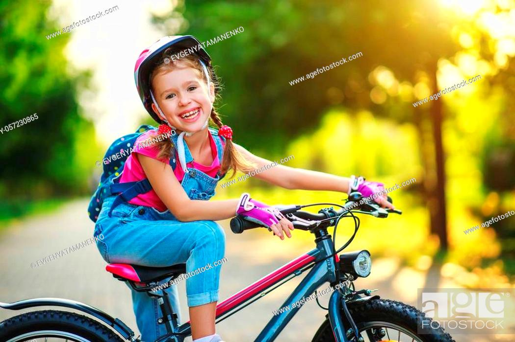 Stock Photo: happy cheerful child girl riding a bike in Park in the nature.