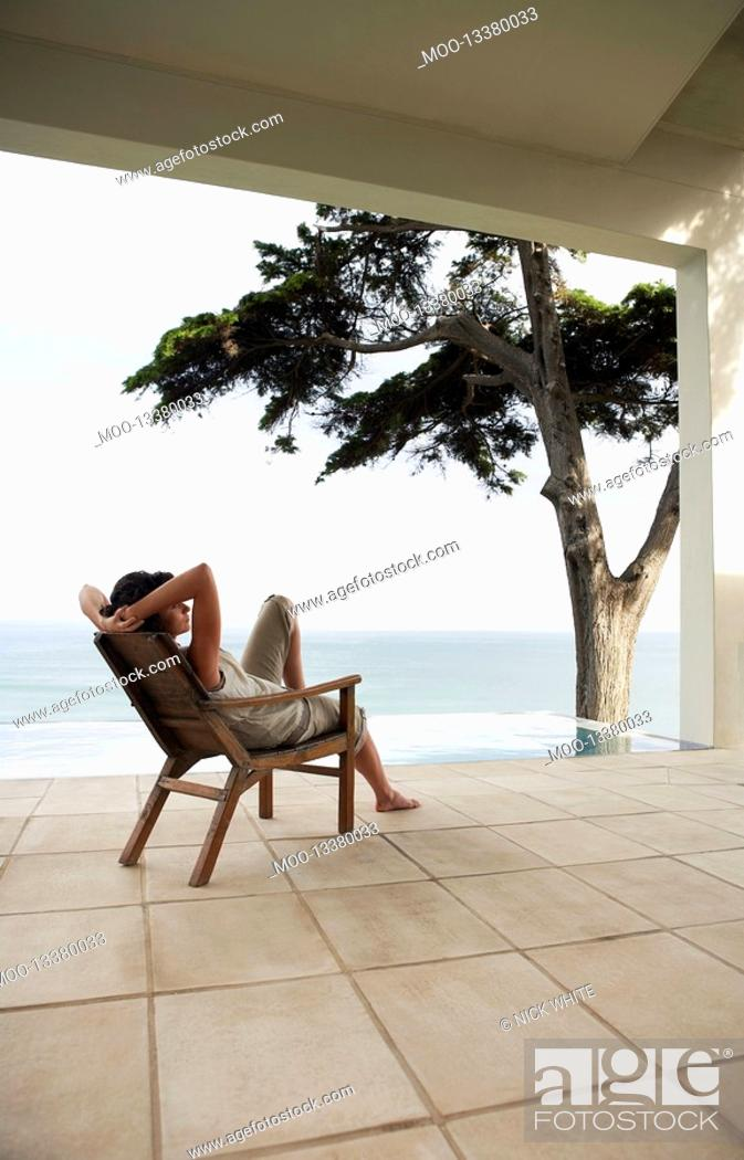 Stock Photo: Woman looking at sea sitting on lounge chair by infinity pool.