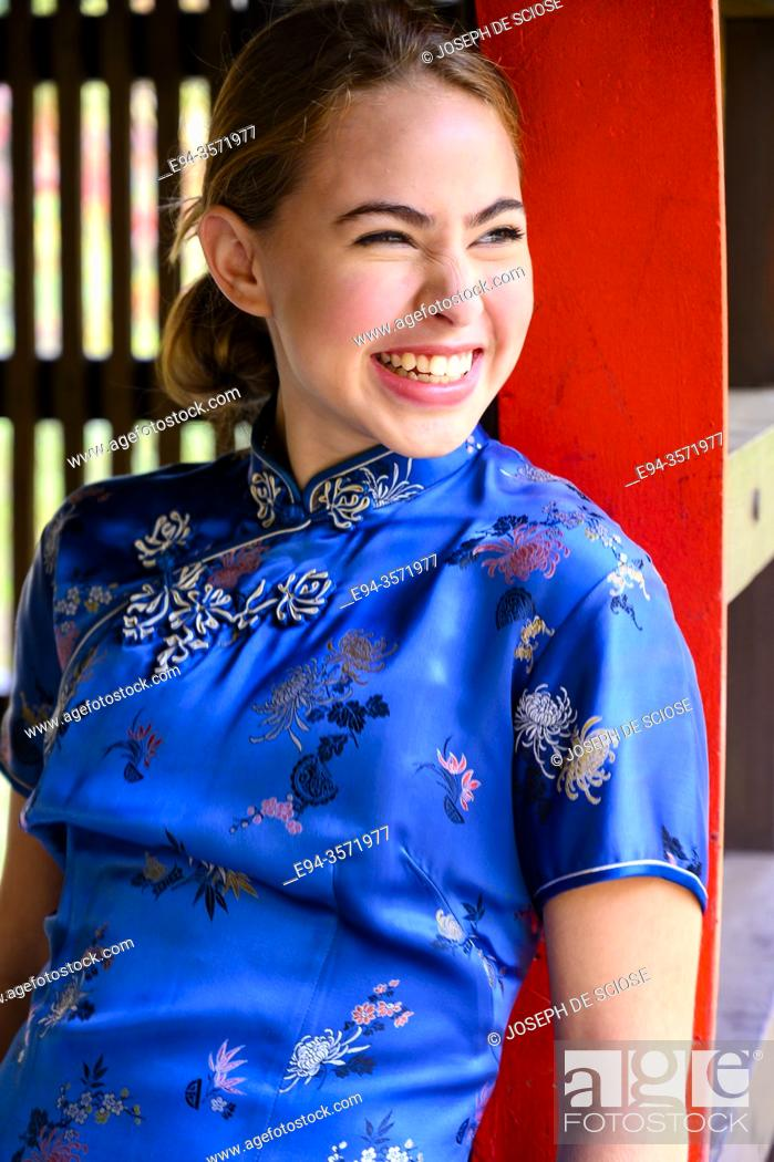 Stock Photo: A laughing 14 year old brunette girl in an asian style dress.