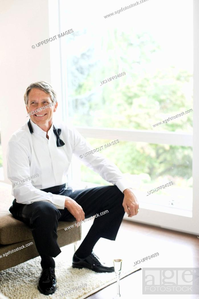 Stock Photo: Man in tuxedo sitting in living room with champagne.