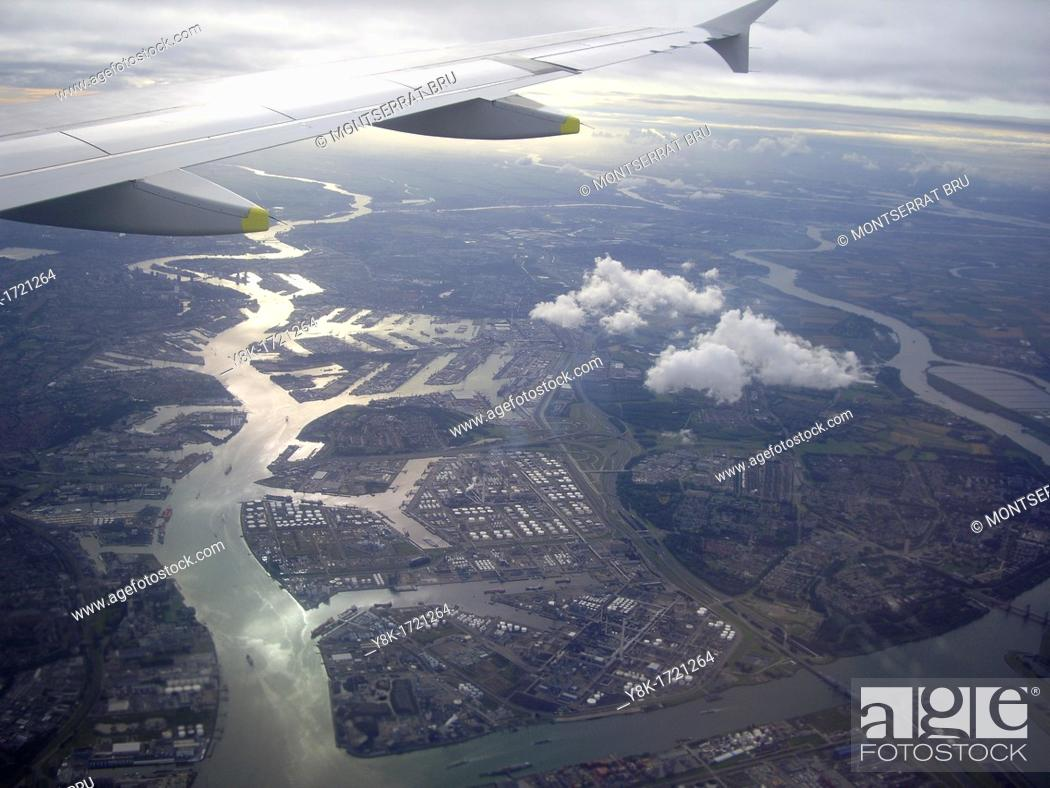 Stock Photo: Aerial view of Port of Rotterdam, The Netherlands, with aircraft wing and clouds in the sunset.