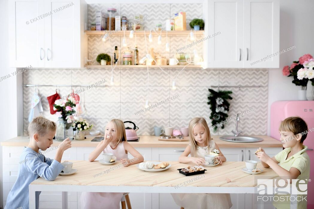 Stock Photo: Four children eating cookies at kitchen table.