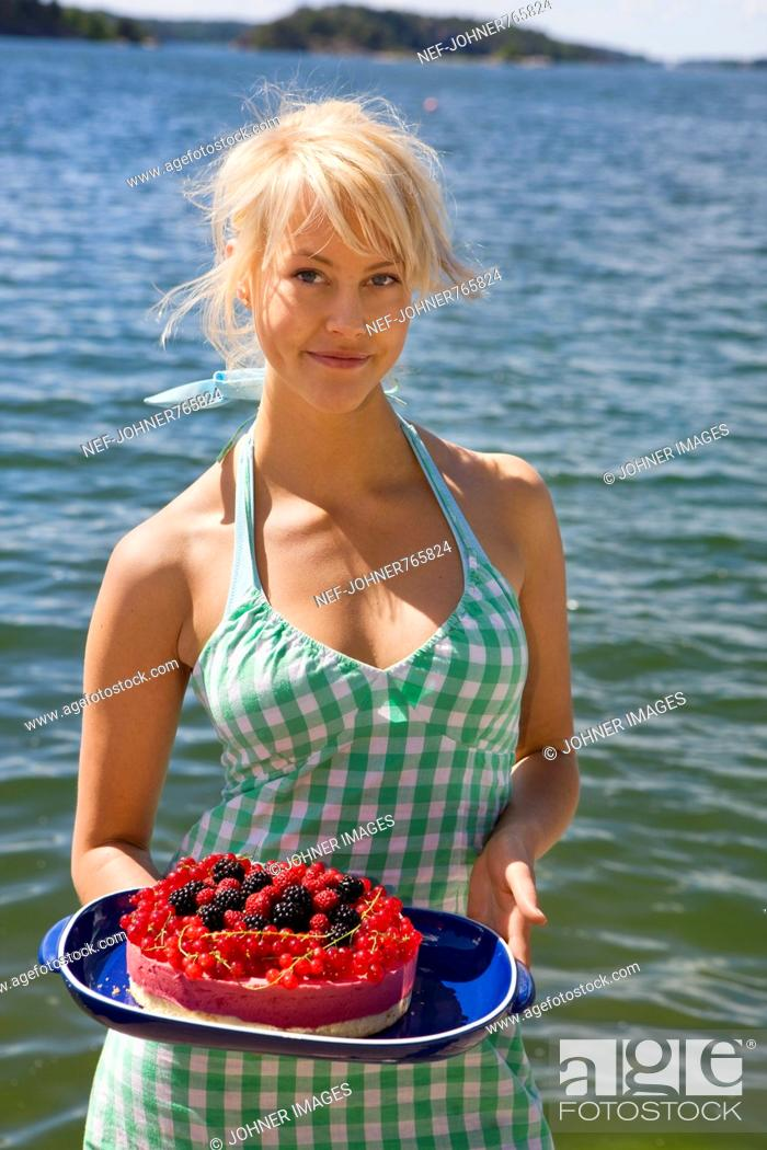 Stock Photo: Young woman holding a cake with different berries, Sweden.