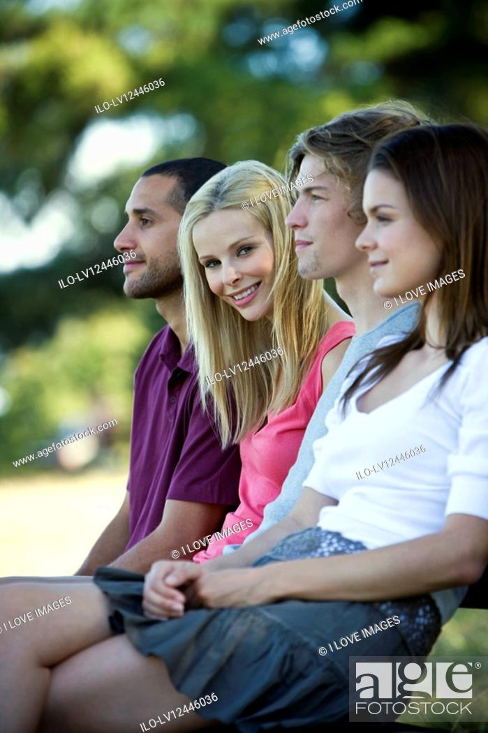 Stock Photo: Four young people sitting on a bench.