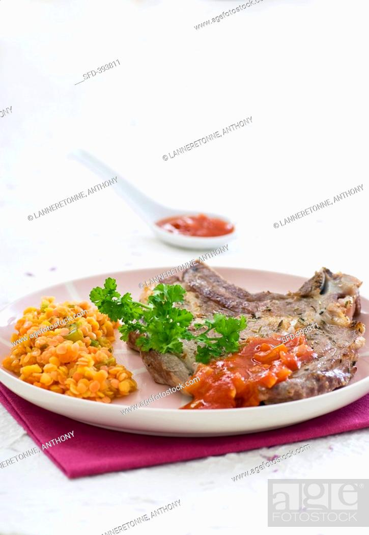 Stock Photo: Veal chop with herbs, tomato sauce and lentils.