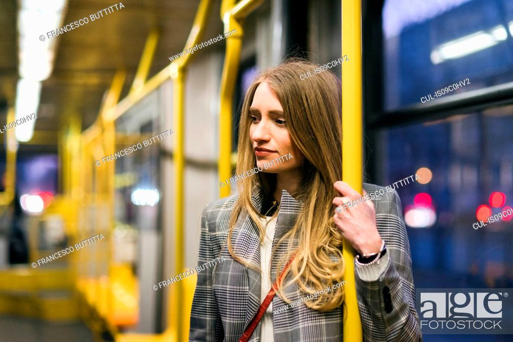 Stock Photo: Young woman with long blond hair standing in train carriage at dusk.