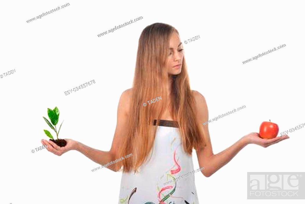 Stock Photo: Beautiful young woman holding green sprout of tree and apple.
