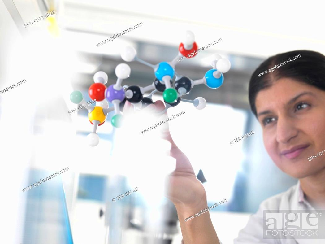 Imagen: Female Asian using a molecular model to understand a chemical formula.
