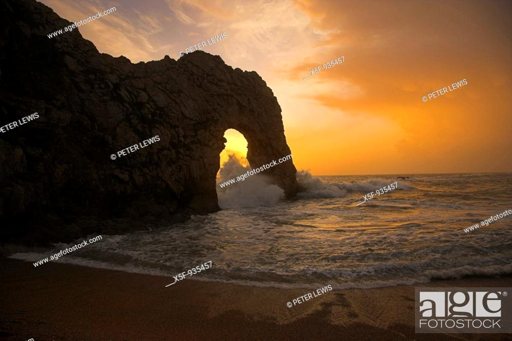 Stock Photo: Sun setting through Durdle Door during rough weather and stormy Sea.