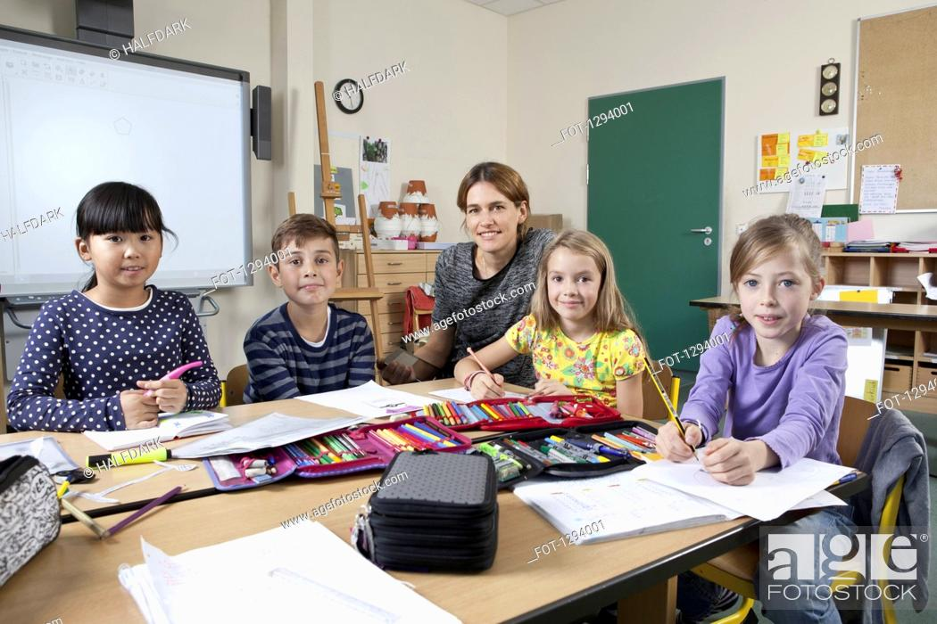 Stock Photo: Teacher with students in classroom, portrait.