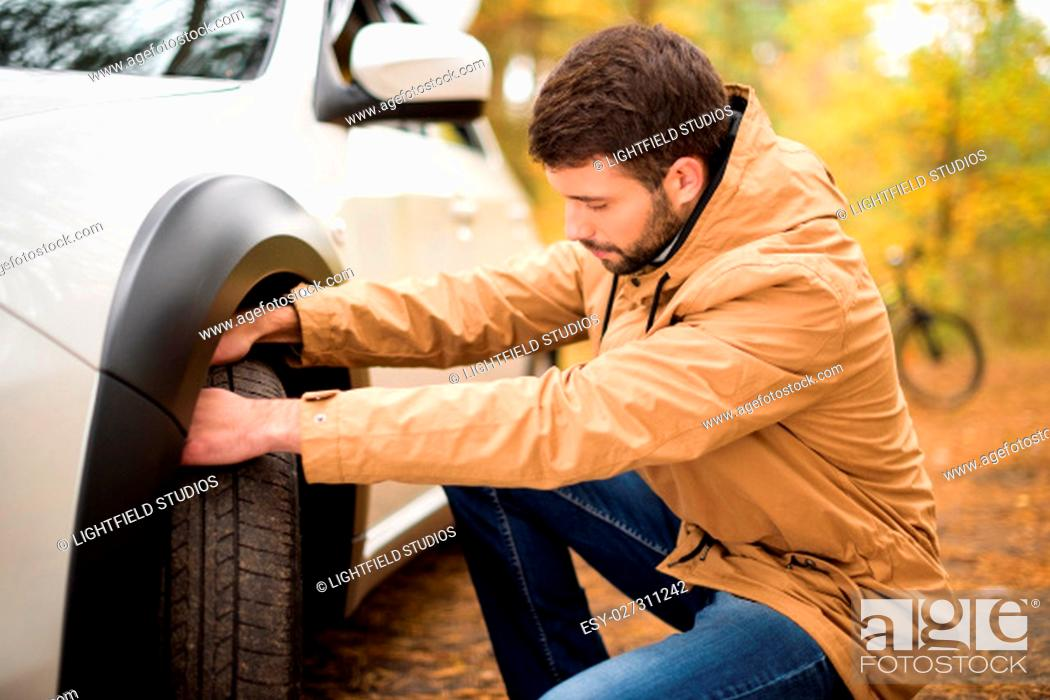 Stock Photo: Young bearded man checking car tyre in autumn forest.