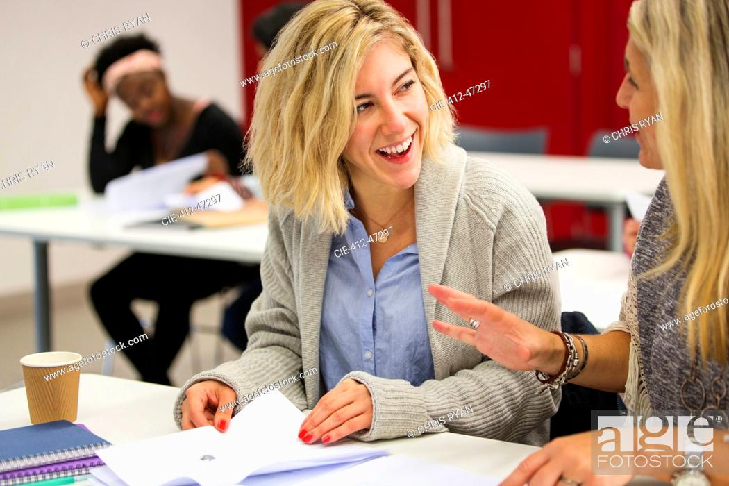 Stock Photo: Female community college students talking, studying in classroom.