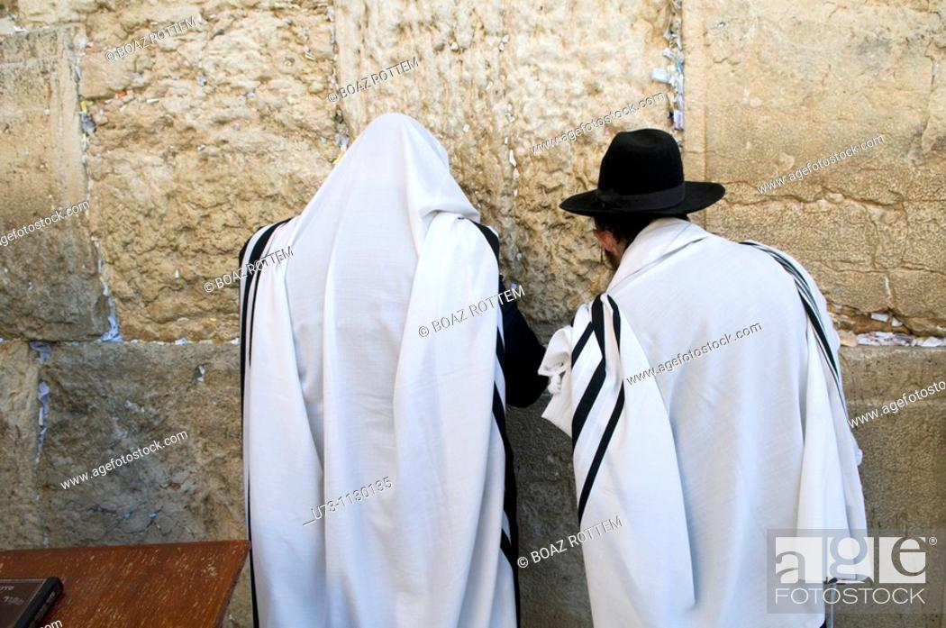 Stock Photo: Jewish men pray by the wailing ( western ) wall of the old temple in Jerusalem.