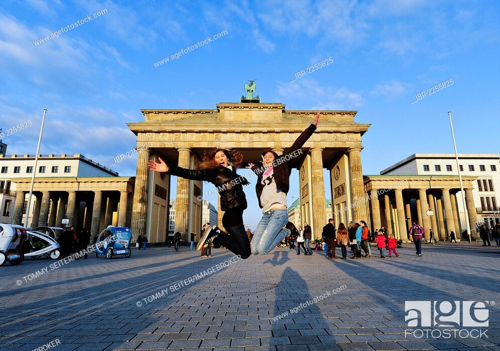 Imagen: Jumping for joy, two girls jumping in the air in front of the Brandenburg Gate, Berlin, Germany, Europe.