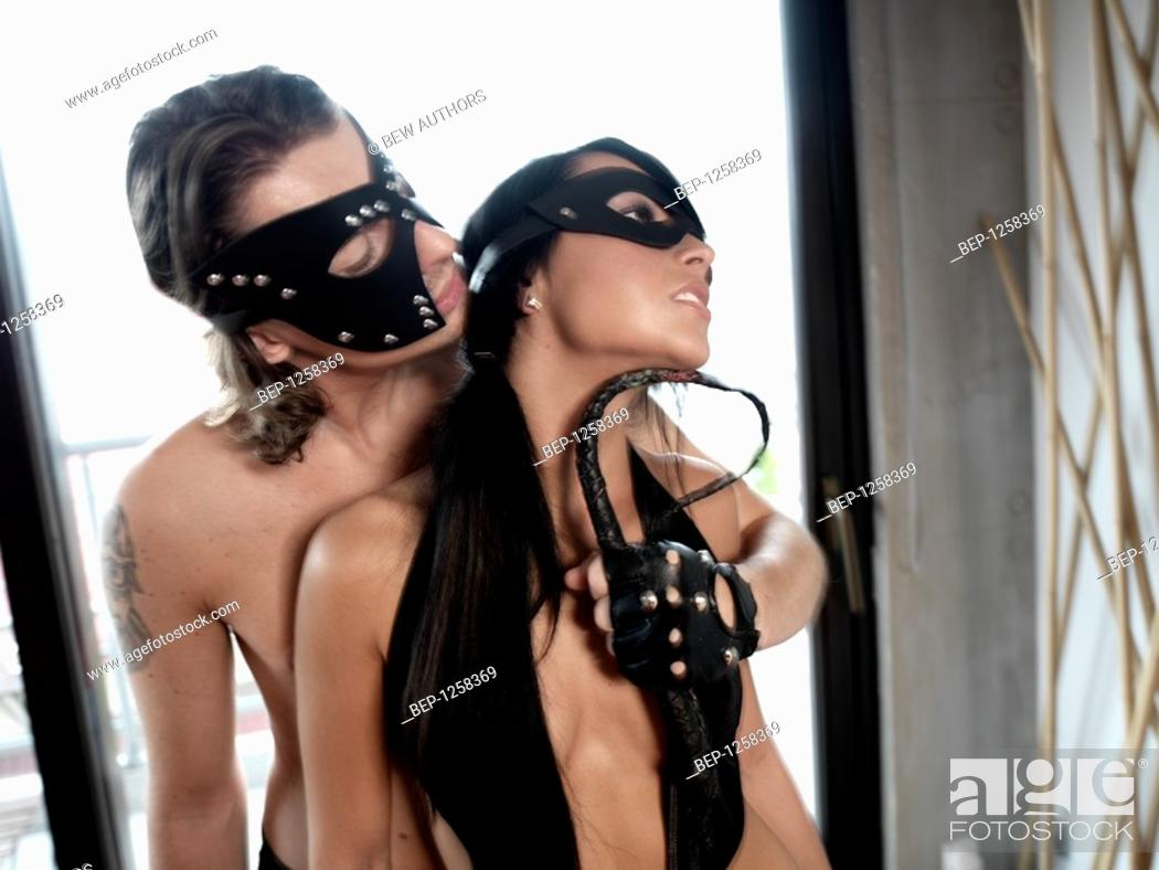 Stock Photo: Man and a woman in leather masks.
